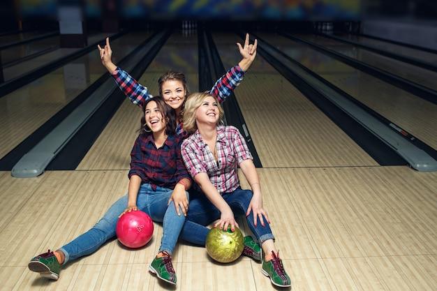 Drei glückliche mädchen, die spaß haben, auf dem boden im bowlingclub sitzend.