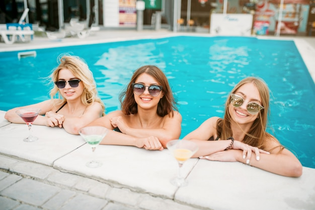 Drei glückliche mädchen in badeanzügen und sonnenbrille am pool. urlaub im resort. frauen im schwimmbad