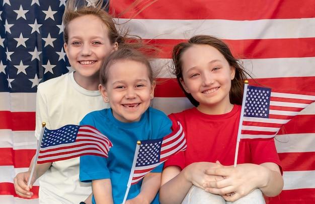 Drei glückliche mädchen mit amerikanischen flaggen in den händen schauen in die kamera und lächeln. der wind entwickelt haare und fahnen. tag der unabhängigkeit. patriotischer feiertag.