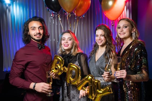 Drei glückliche mädchen und junger mann, die flöten des champagners und der luftballons halten, während geburtstag im nachtclub feiern