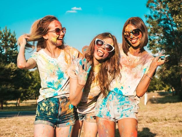 Drei glückliche schöne mädchen machen party am holi farben festival