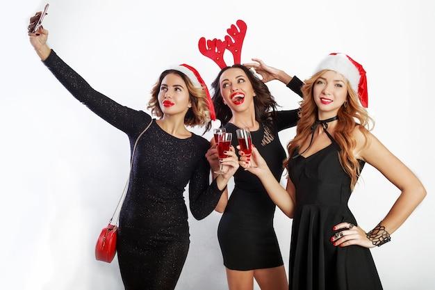 Drei glückliche stilvolle mädchen verbringen zeit auf verrückter party, tanzen, haben spaß und lachen. tragen sie ein elegantes freizeitkleid und maskeradenhüte für das neue jahr. fotos machen.