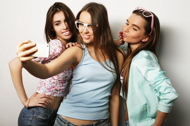 Drei glückliche teenager-mädchen mit smartphone nehmen selfie