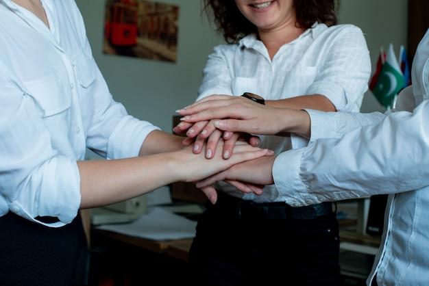Drei glückliche zufriedene weibliche büroangestellte, die fröhlich lächelten, stapelten fröhlich ihre hände zusammen geste der einheit der freundschaft und der partnerschaft im geschäft, das im amt steht