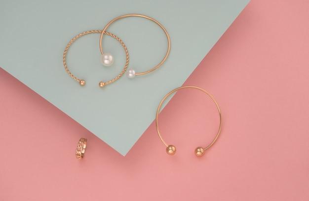 Drei goldene armbänder und ring auf pastellfarbenen papieren