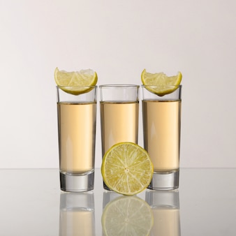 Drei goldene tequila-schüsse mit kalk auf weißem hintergrund