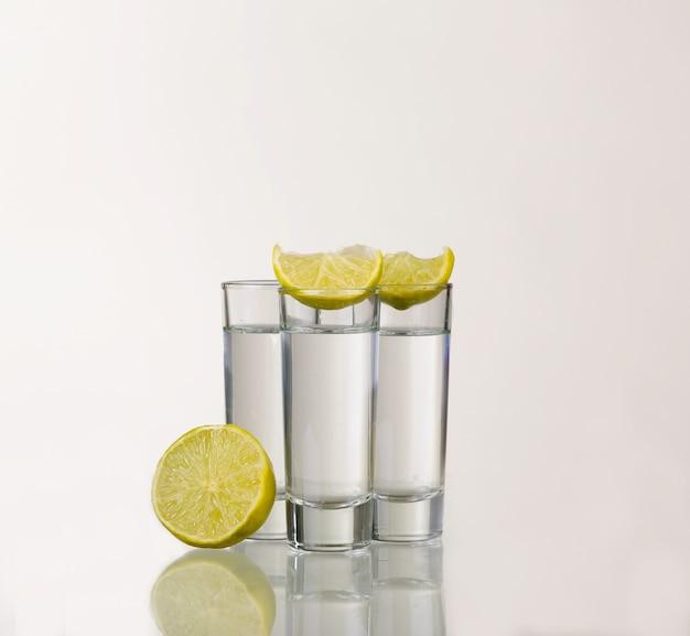 Drei goldene tequila-schüsse mit kalk lokalisiert auf weiß