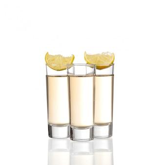 Drei goldene tequila-schüsse mit kalk lokalisiert auf weißem hintergrund