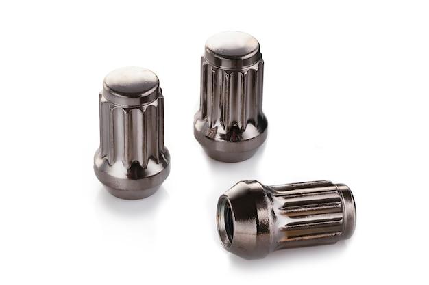 Drei grau glänzende muttern für leichtmetallräder und automatische abstimmung auf einem weißen isolierten hintergrund.