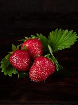 Drei große erdbeeren liegen auf einem dunklen holzhintergrund. unaufdringlich.