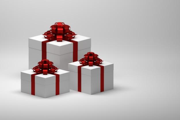 Drei große geschenke geschenke mit roten glänzenden schleifen auf weißer oberfläche
