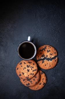 Drei große kekse und eine tasse kaffee auf einer schwarzen betonoberfläche. ein keks ist in zwei teile zerbrochen kekse mit schokoladebild zur beschriftung