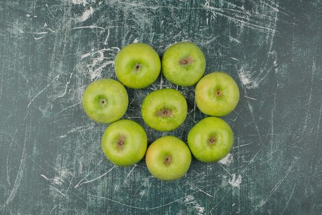 Drei grüne äpfel auf marmoroberfläche.