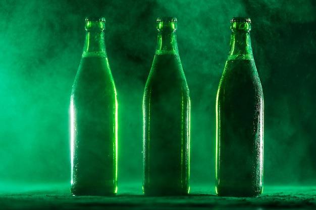 Drei grüne bierflaschen auf einem staubigen hintergrund.