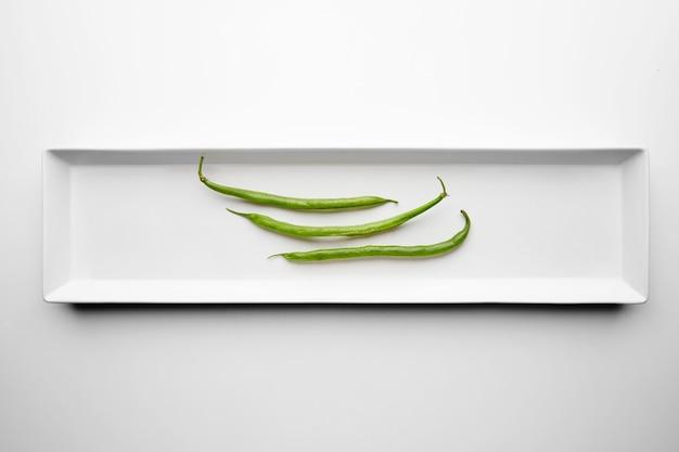 Drei grüne bohnen isoliert in der mitte der rechteckigen weißen keramikplatte auf tisch