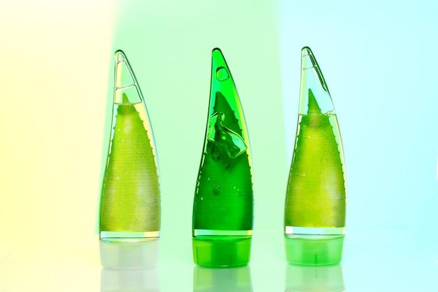 Drei grüne flaschen make-up. umweltfreundliches gel, shampoo und creme