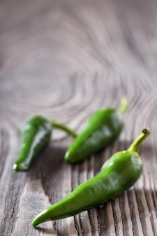 Drei grüne peperoni auf einem holztisch