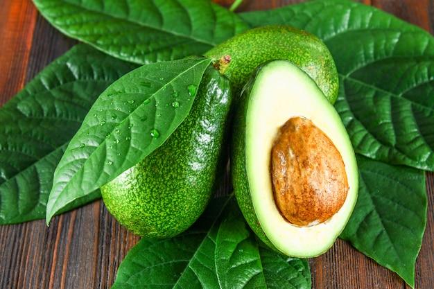 Drei grüne rohe reife avocadofrüchte und ein schnitt halb mit einem knochen mit blättern auf einem braunen holztisch.