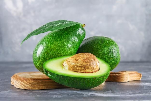Drei grüne rohe reife avocadofrüchte und ein schnitt halb mit einem knochen mit blättern