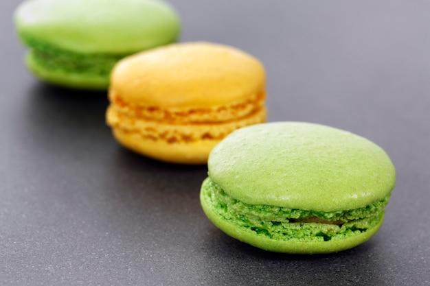 Drei grüne und gelbe makronen in der küche