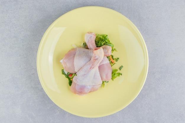 Drei hähnchenschenkel und grün, in der platte, auf der weißen oberfläche
