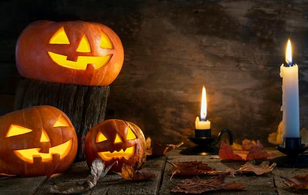 Drei halloween-kürbishauptsteckfassung o-laterne auf holztisch.