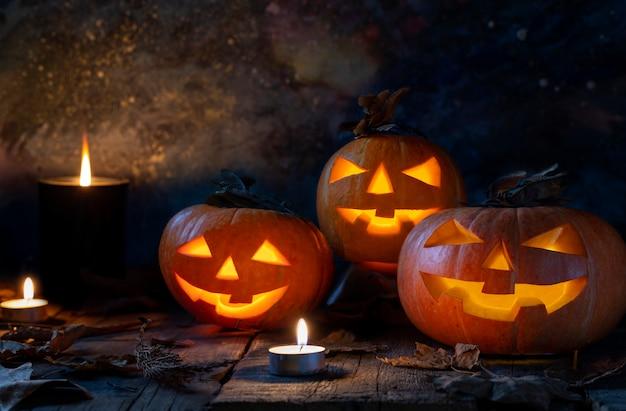 Drei halloween-kürbiskopfsteckfassung o-laterne auf holztisch