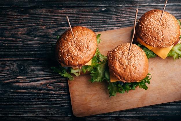 Drei hamburger mit fleisch, käse, salat, tomate auf einem brett auf einem holztisch