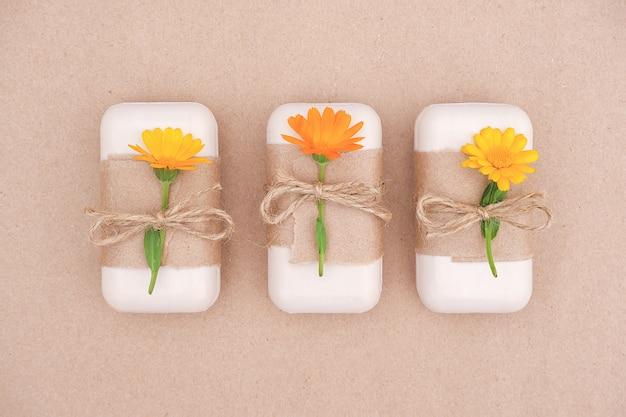 Drei handgefertigte naturseifensets, verziert mit bastelpapier, geißel und orangefarbenen ringelblumen. bio-kosmetik,