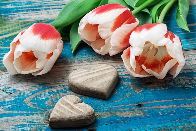 Drei handgeschnitzte herz aus holz mit strauß tulpen