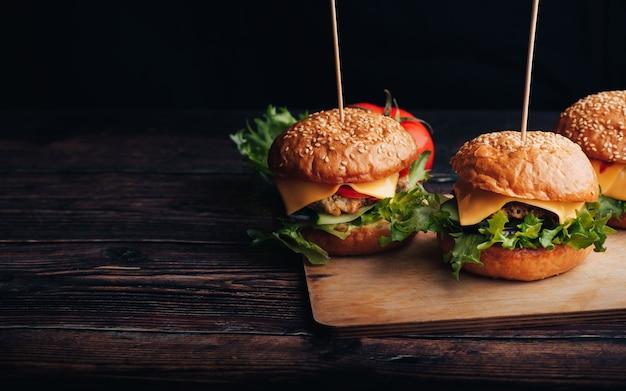 Drei hausgemachte hamburger mit fleisch, käse, salat, tomate auf einem holzbrett auf einem tisch