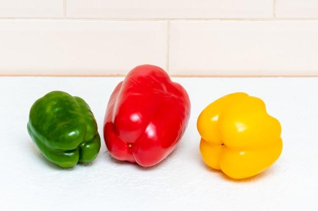 Drei helle bulgarische paprika rot gelb und grün auf dem küchentisch