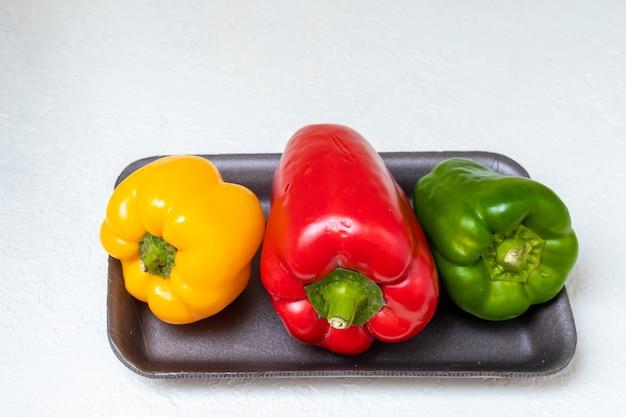 Drei helle bulgarische paprika rotgelb und grün in einem behälter auf einer hellen oberfläche, nahaufnahme.