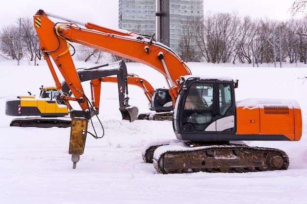 Drei helle raupenbagger parken auf einem verschneiten feld, ausleger und stiele bilden eine enfilade