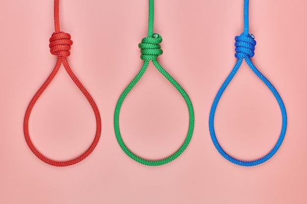 Drei henker-knoten. anstiftung zum selbstmord oder zur todesstrafe. rote, grüne und blaue geflochtene hängende schlinge banden den knoten.