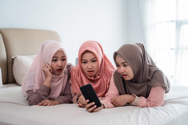 Drei hijab frau, die auf dem bett liegt, verblüfft aussehendes smartphone