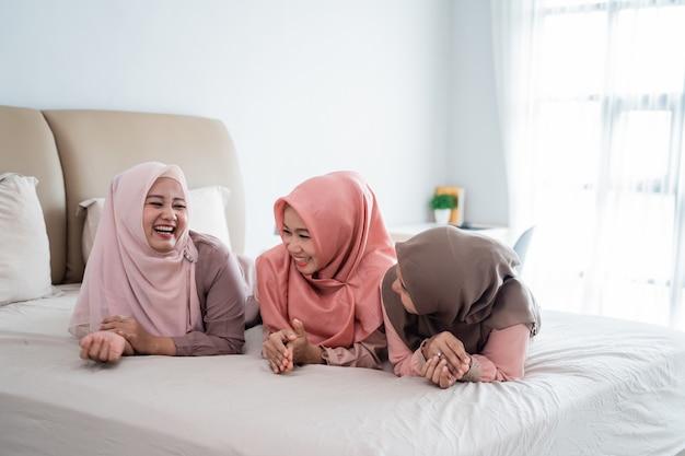 Drei hijab-frauen, die auf dem bett liegen und miteinander reden und plaudern