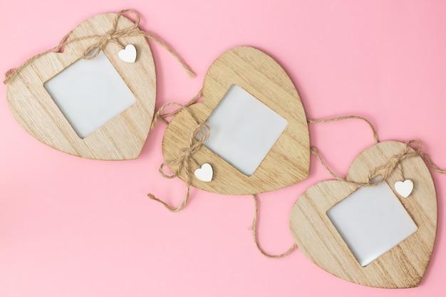 Drei hölzerne herzförmige fotorahmen auf einem rosa hintergrund. flach liegen. speicherplatz kopieren.