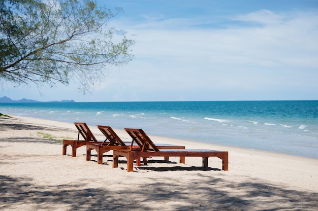 Drei hölzerne sonnenliege am strand im tropischen meer zur sommerzeit