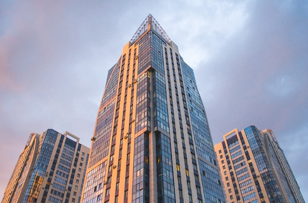 Drei hohe wohngebäude bei sonnenuntergang.