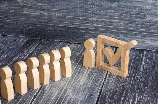Drei holzfiguren stehen neben einem häkchen im kasten