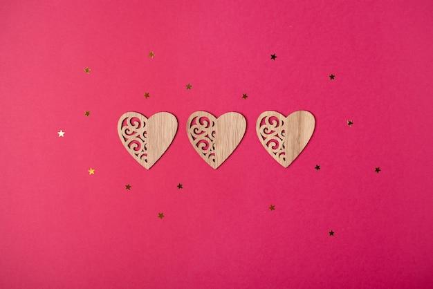 Drei holzherzen und kleine goldene sterne. valentinstag konzept. flache lage, draufsicht.