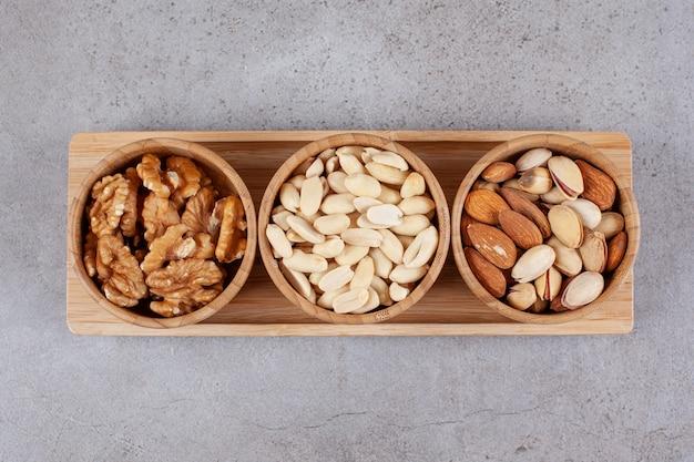 Drei holzschalen mit verschiedenen gesunden nüssen