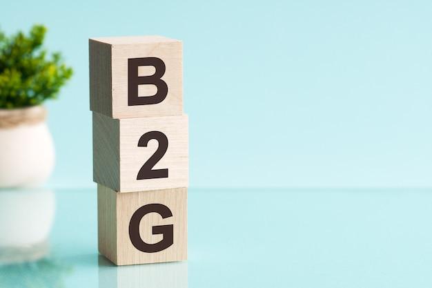 Drei holzwürfel mit buchstaben - b2g - abkürzung für business to government, auf blauem tisch