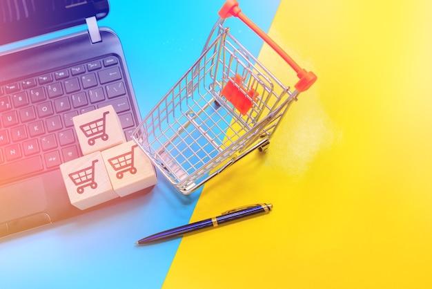 Drei holzwürfel mit dem bild eines einkaufswagens auf einer laptoptastatur. online-shopping- und lieferkonzept