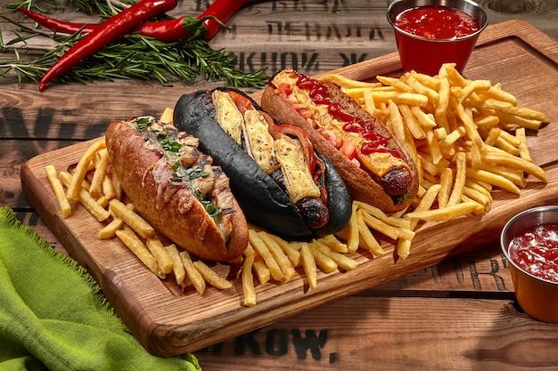 Drei hotdogs auf holzbrett mit pommes frites und soße