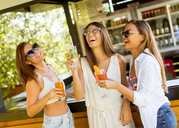 Drei hübsche junge frauen trinken coctais in der strandbar