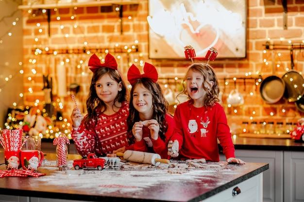 Drei hübsche junge mädchen im roten weihnachtspyjama und in den stirnbändern, die kekse in der küche mit weihnachtshintergrund machen.