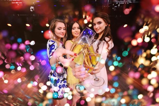 Drei hübsche junge mädchen mit gläsern champagner