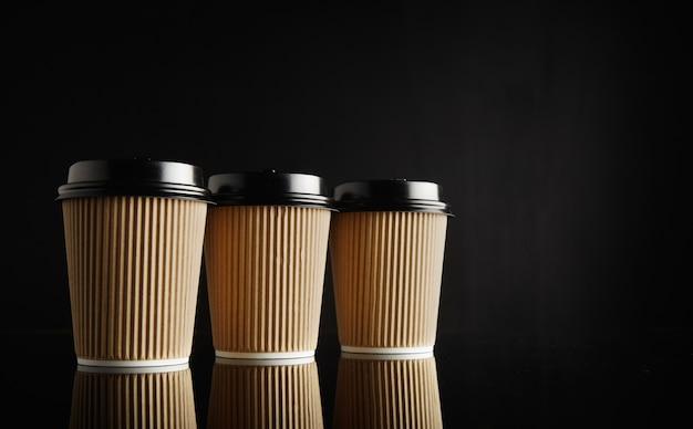 Drei identische hellbraune pappkaffeetassen zum mitnehmen mit schwarzen deckeln in einer reihe auf einem reflektierenden schwarzen tisch gegen eine schwarze wand